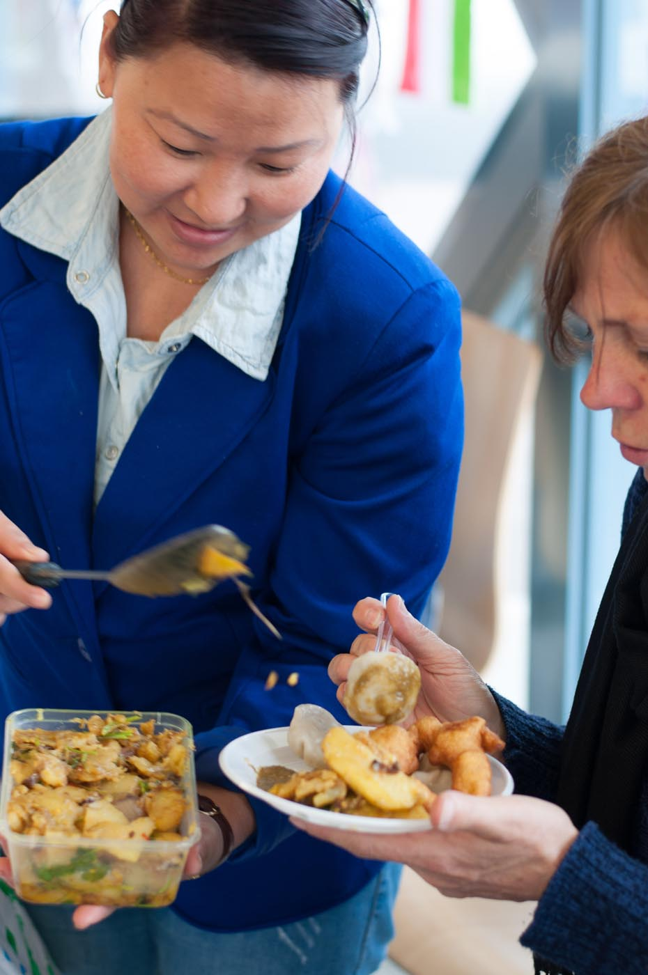 Photo of a lady holding a container of a dish placing a serve onto another person's plate - click to view larger image