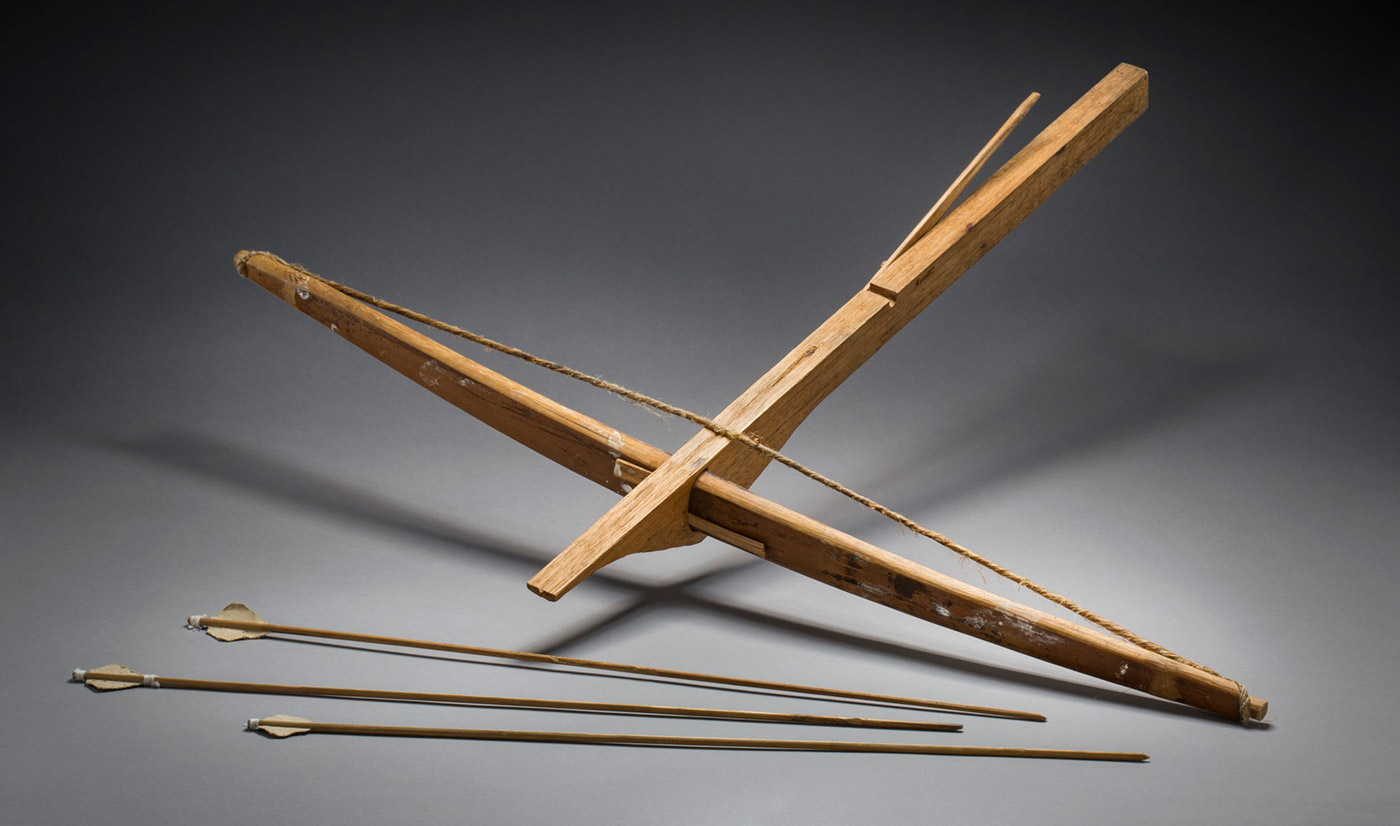A homemade light brown wooden cross bow with bark string. The main body of the bow has a straight top edge with a horizontal groove to hold the string and a vertical groove to guide the arrow. A flat stick of wood shaped to a rounded point is attached to the side of the main body, just behind the horizontal groove, with a wooden pin. The underside of the main body is curved with a rectangular hole to hold the cross piece. The crosspiece is a long slim flat slightly eliptical shape which is inserted in the rectangular hole. Two small wedges have been used to secure the crosspiece. A string made from strips of bark tightly wound together by hand is attached at each end of the cross piece. There are spots and smudges of a white substance on the front of the crosspiece. - click to view larger image