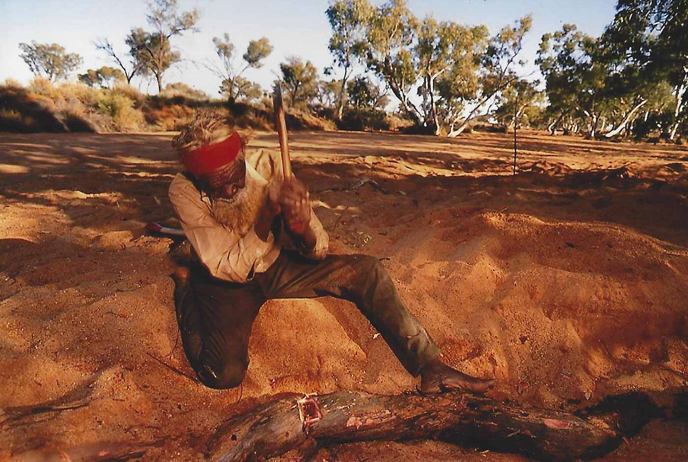 A photo of a man chopping a piece of tree wood with an axe. - click to view larger image