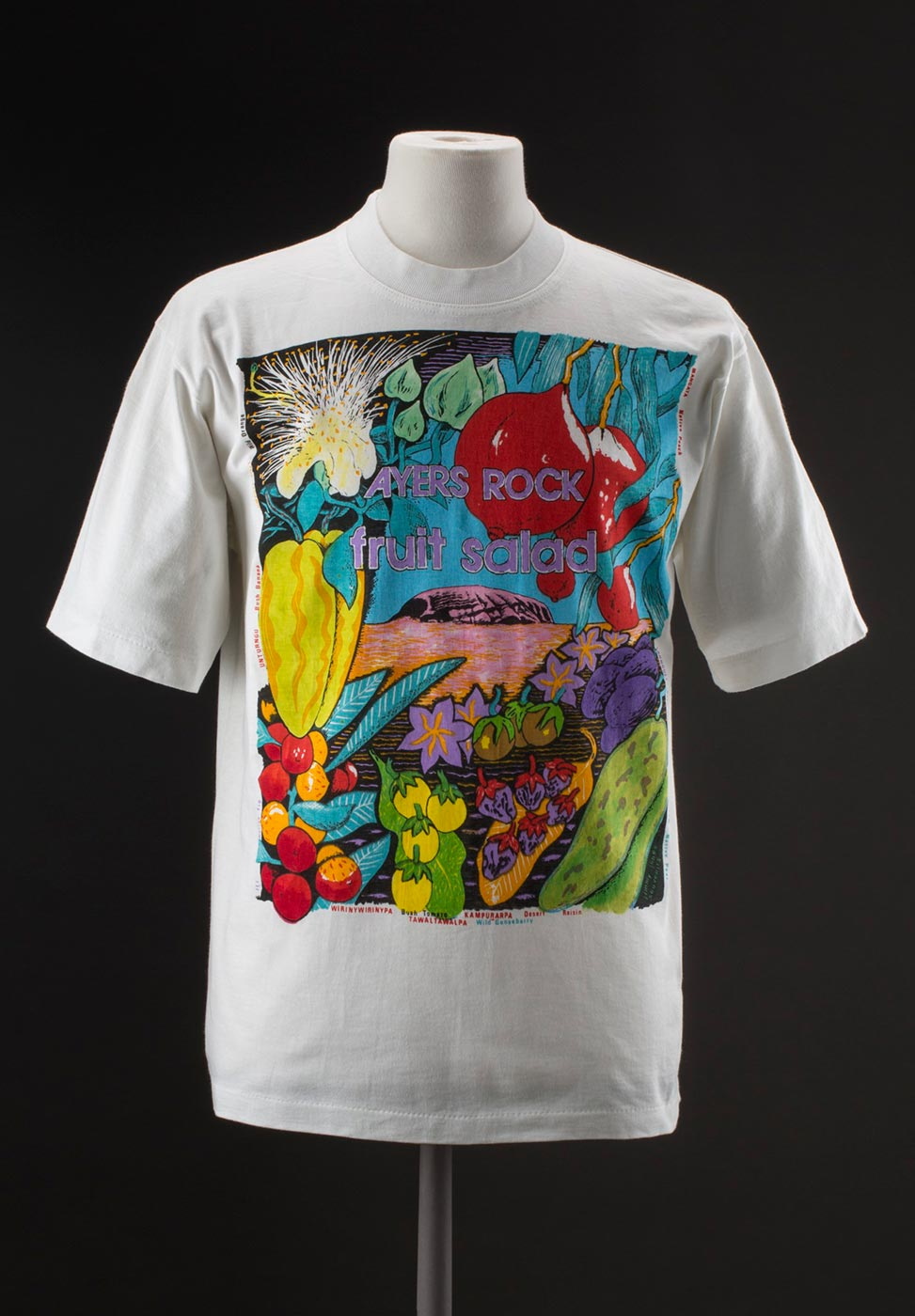 T-shirt with colour illustration of fruits around a central image of Uluru. - click to view larger image