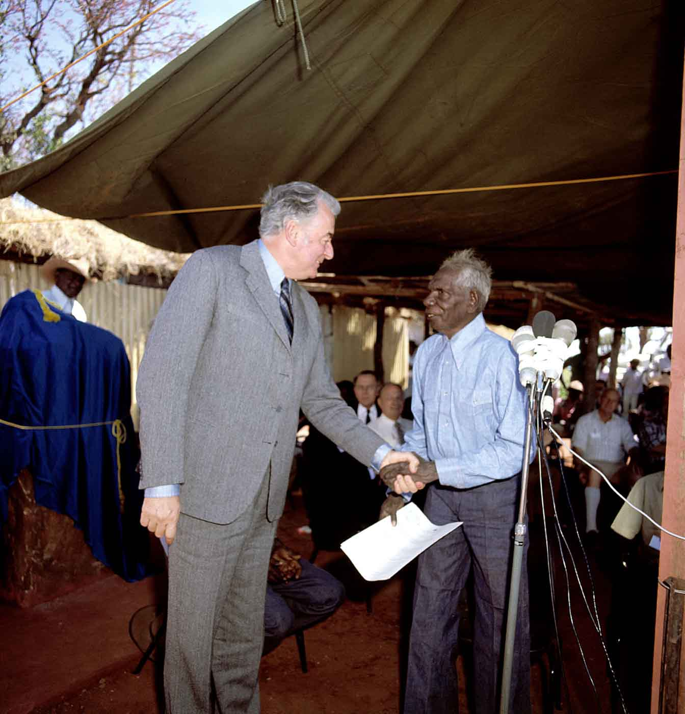 Two men are standing under a canvas roof in outback terrain. One man is Gough Whitlam who is shaking Vincent Lingiari's hand.