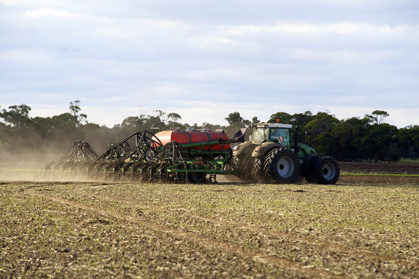 A farming contractor sowing farmland.