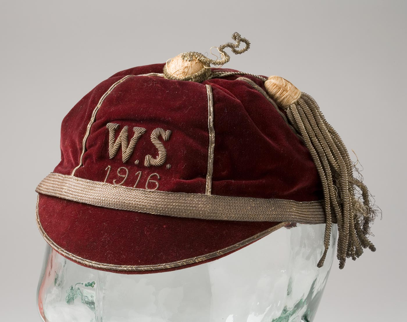 Maroon cap embroidered with 'WS 1916'. - click to view larger image