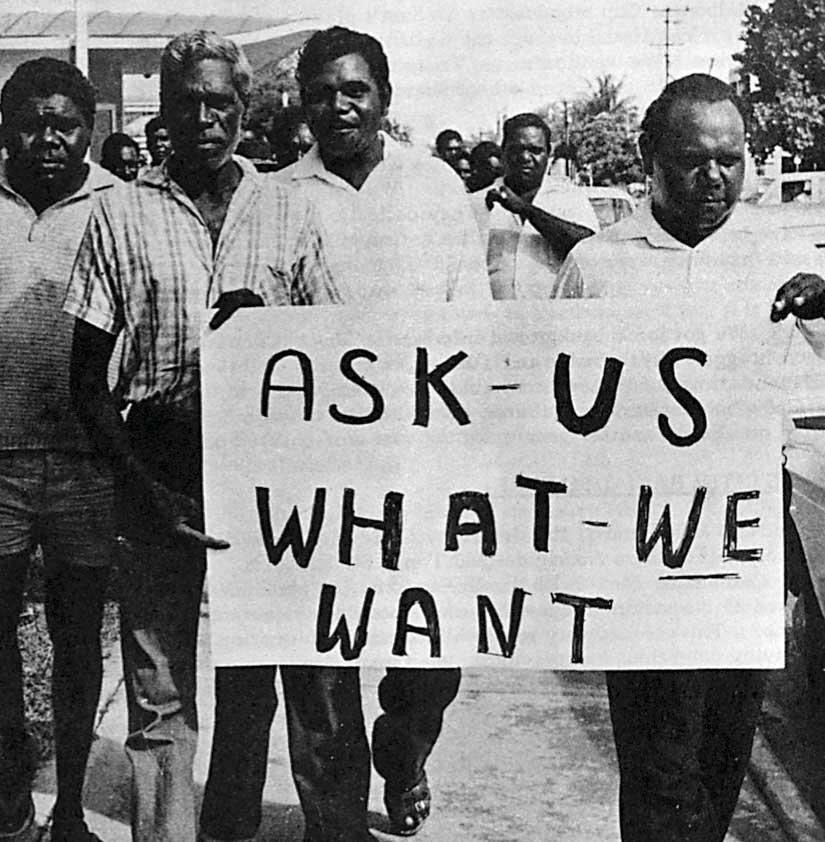 Black and white photo of a large group of men carrying a banner which reads: 'ASK - US WHAT - WE WANT.' - click to view larger image