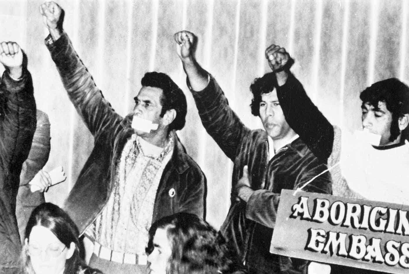 Black and white photo of protesters holding their arms up in salute. Two men have their mouths taped and one is holding a sign that reads: 'ABORIGINAL EMBASSY' - click to view larger image