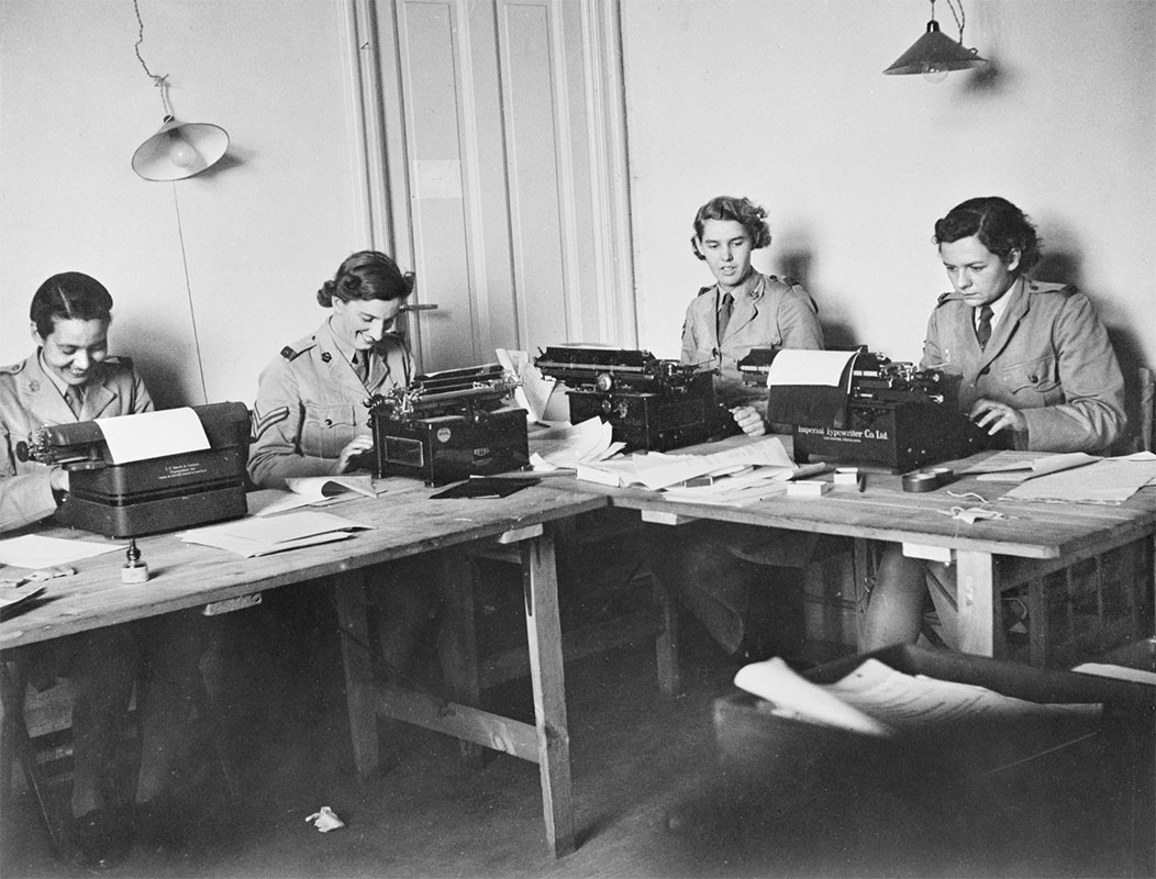 A black and white photograph of four women dressed in military uniform sitting on the far side of two tables placed together in an L-shape in the corner of a room. Two sit at each table and all four are working at typewriters. Sheets of paper, a sheet of carbon paper, pens and various other items of office stationery are visible on the tables. There is a panelled wooden door behind the women. - click to view larger image