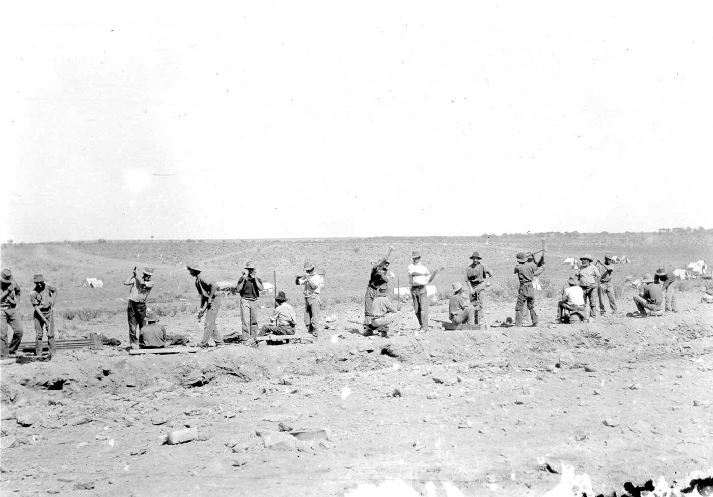 A black and white photo of railway construction workers in the desert.