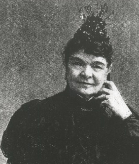 Black and white portrait photo of a woman seated and wearing black attire. - click to view larger image