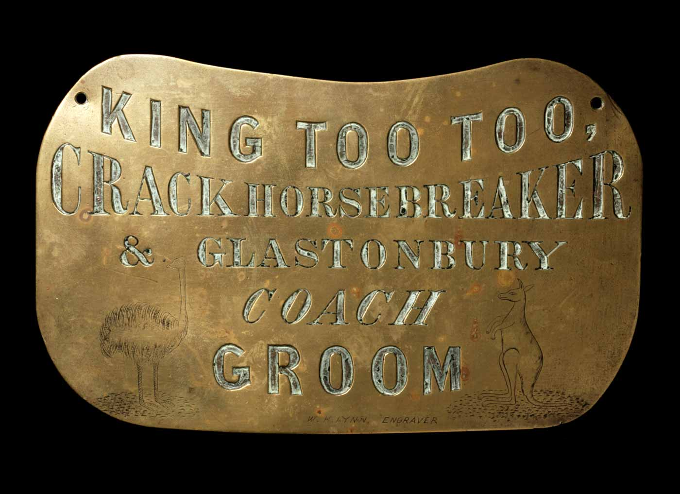 Breastplate engraved with text 'King Too Too, crack horsebreaker & Glastonbury coach and groom' and images of a kangaroo and emu. - click to view larger image