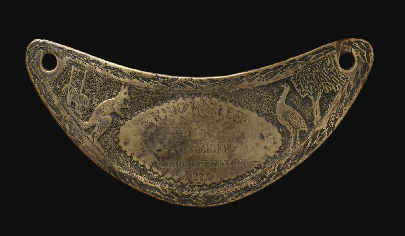 Engraved crescent-shaped breastplate with images of a kangaroo and emu, tree and plants. - click to view larger image