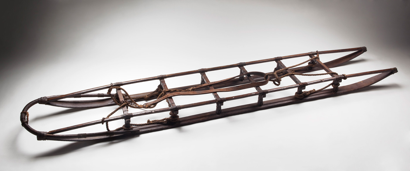 A lowline wooden sled with six cross-braces and various ropes and leather straps attached to the top.
