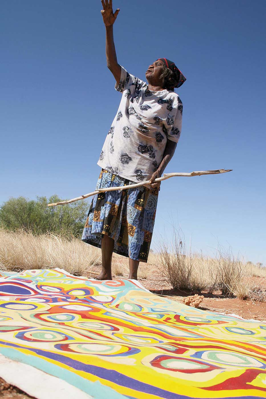 Colour photo of a woman standing on arid land behind a painting. She is holding a stick and pointing upwards with her right arm. - click to view larger image