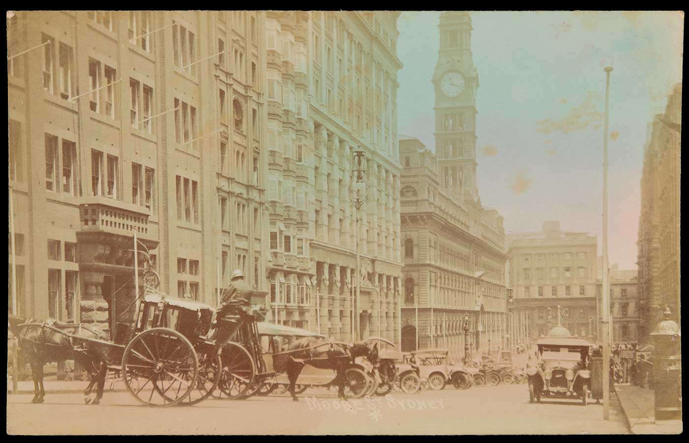 Sepia photograph showing a city street, with a series of motor vehicles and two horses and carts at the kerb, outside a row of multi-storey buildings.  - click to view larger image