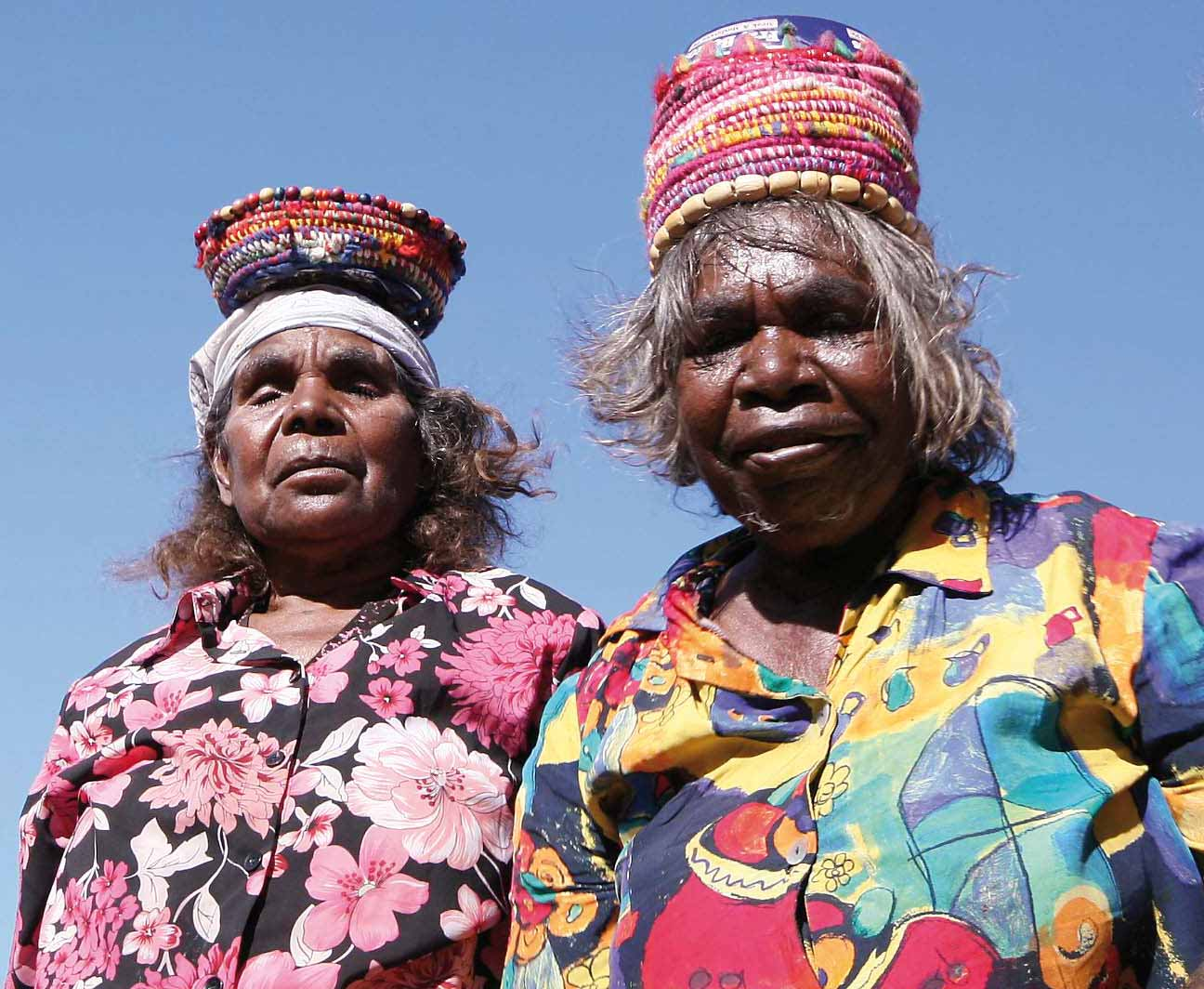 Colour photograph of two women with colourful woven baskets on their heads.