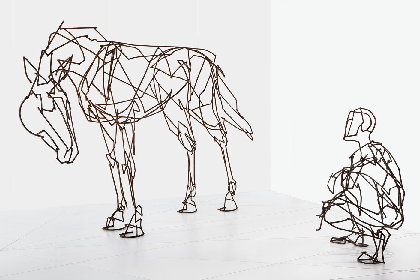 Metal sculpture showing a person squatting away and to the side of the form of a horse.