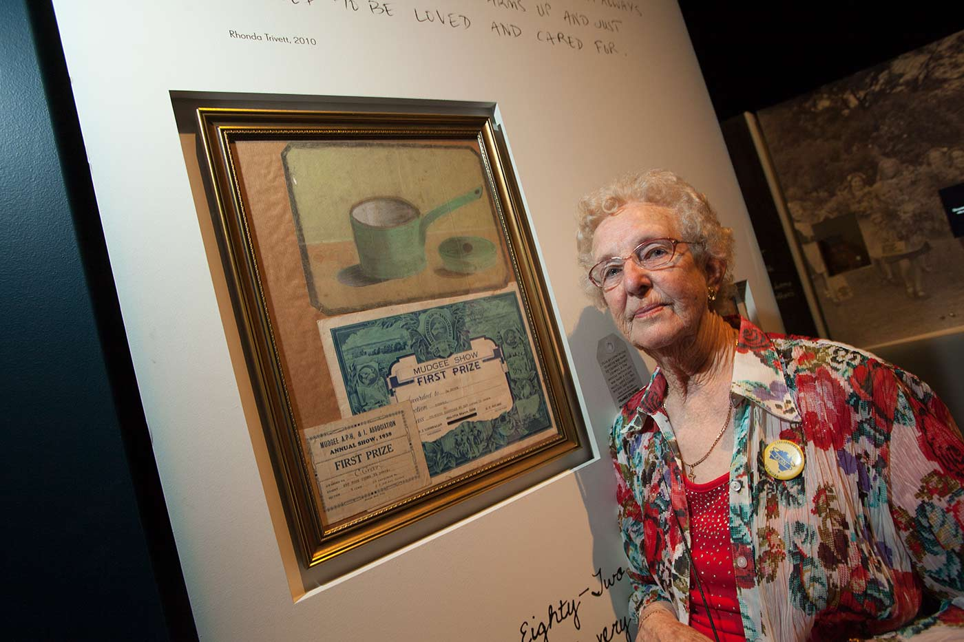 Colour photograph showing a woman standing beside a framed painting and two prize certificates.  - click to view larger image