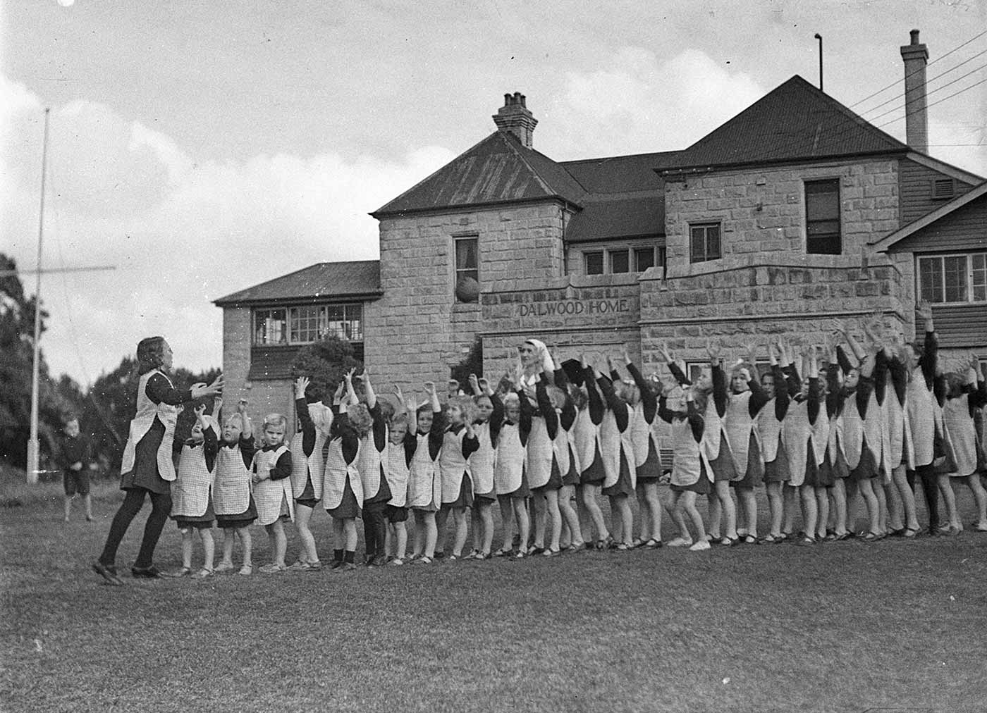 Black and white photograph showing a side view of a long line of girls, standing in front of a large sandstone building which has 'DALWOOD HOME' inscribed on one side. An older girl reaches forward after throwing a ball above the other girls' outstretched arms. A woman wearing a white veil stands about halfway down the line, behind the girls. Each of the girls wears an apron over a dress. - click to view larger image