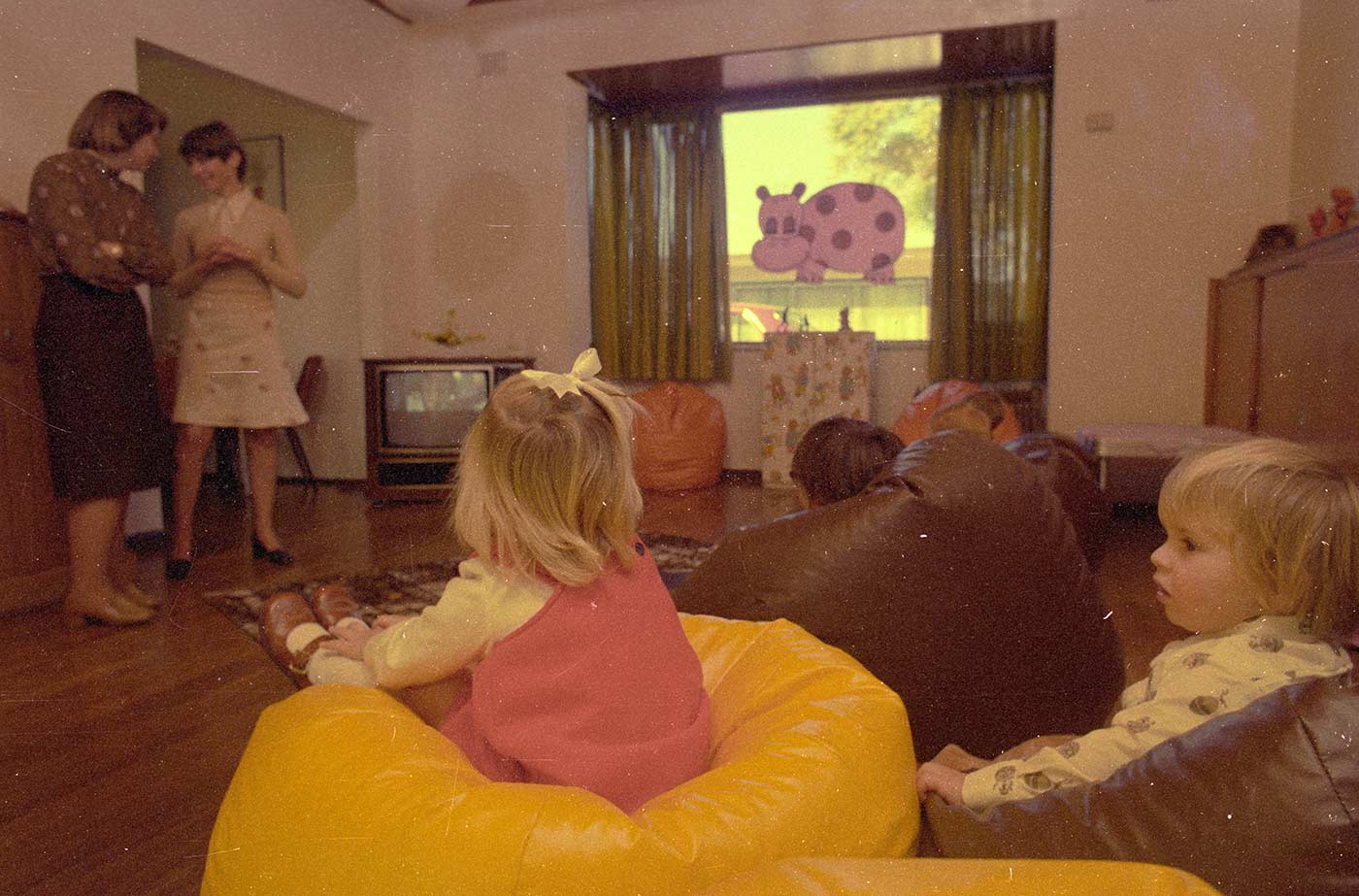 Colour photograph showing a side and rear view of five small children sitting on beanbags, watching a television in the opposite corner. Two women stand talking at the left of the image. A purple hippopotamus transfer is seen on a window at the far end of the room. - click to view larger image