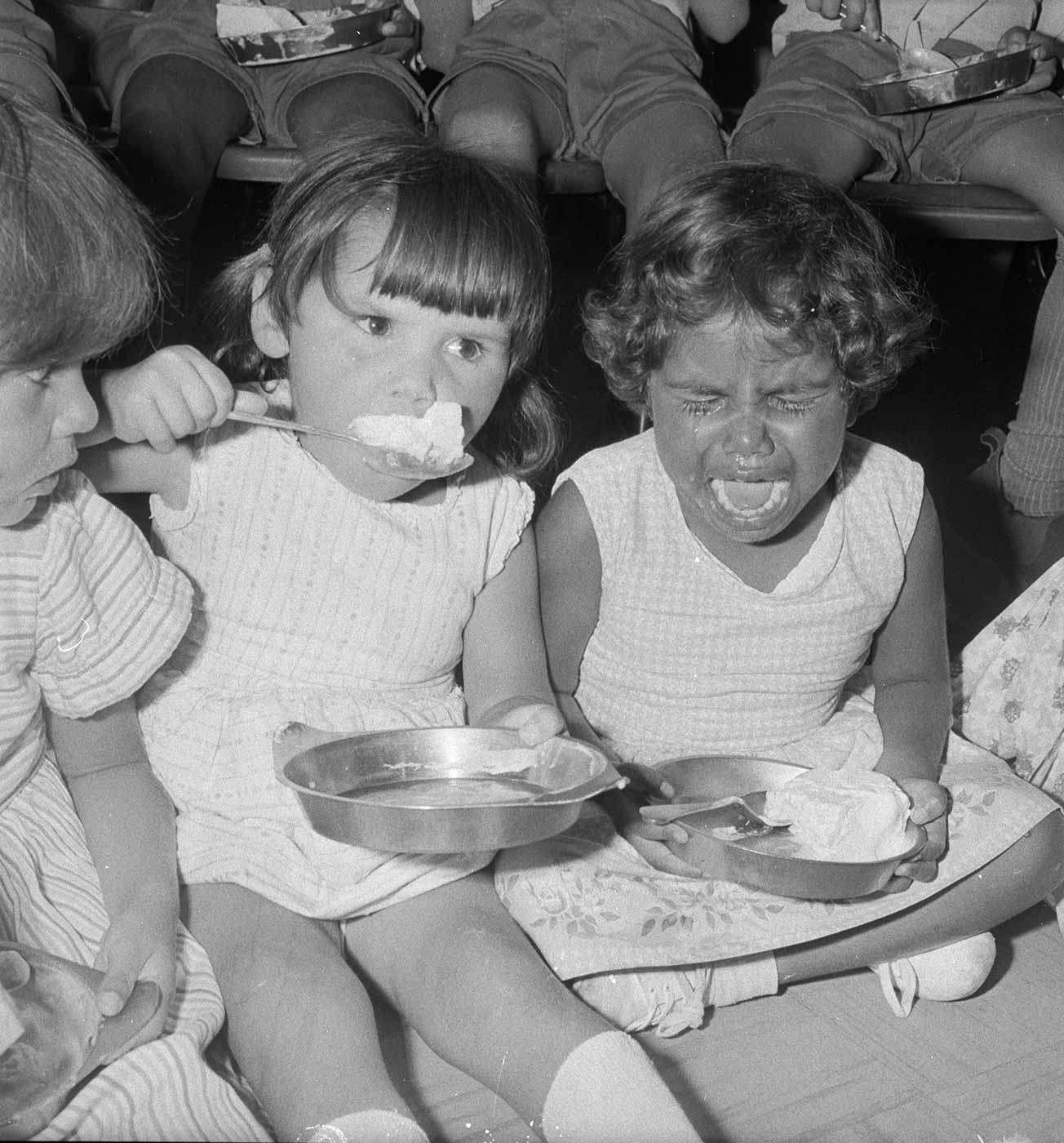 Black and white photo showing three young girls icecream in metal bowls. A young Aboriginal girl on the right is crying. The girl at centre holds a spoon with icecream to her mouth, and a girl partially visible on the left stares at the distressed girl. - click to view larger image