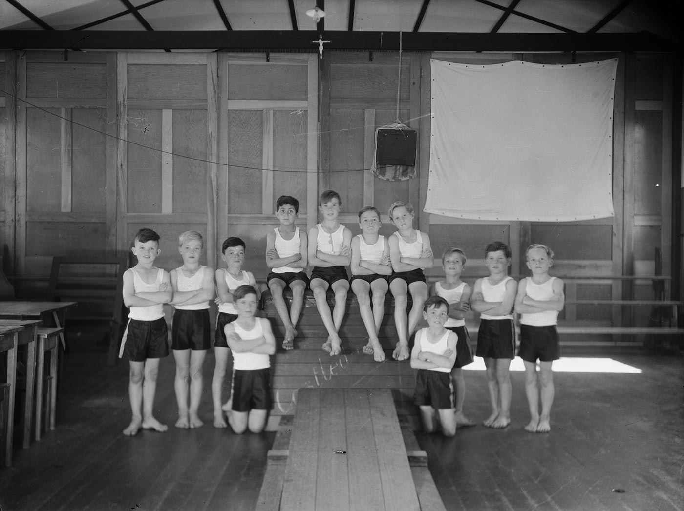 Black and white photograph showing 12 young boys, wearing dark shorts and white singlets. Four of the boys sit with crossed arms and ankles on a vaulting horse at the centre. Three other boys stand, cross-armed, either side and two kneel at the front. - click to view larger image