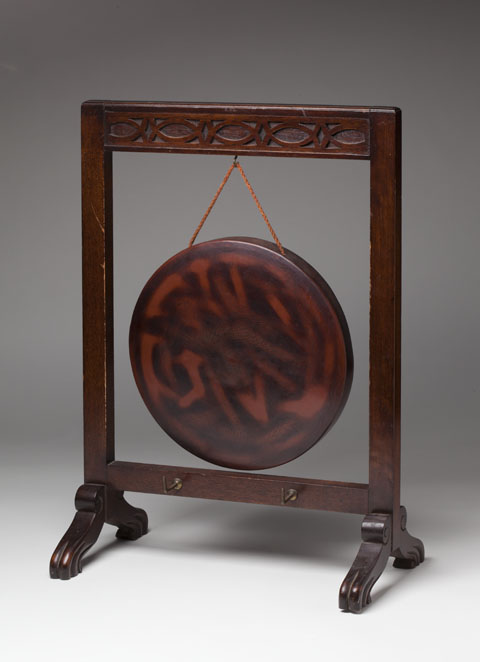 A circular gong in shades of brown, engraved with a bird and with  leaf patterns, suspended by a string from a timber frame. - click to view larger image