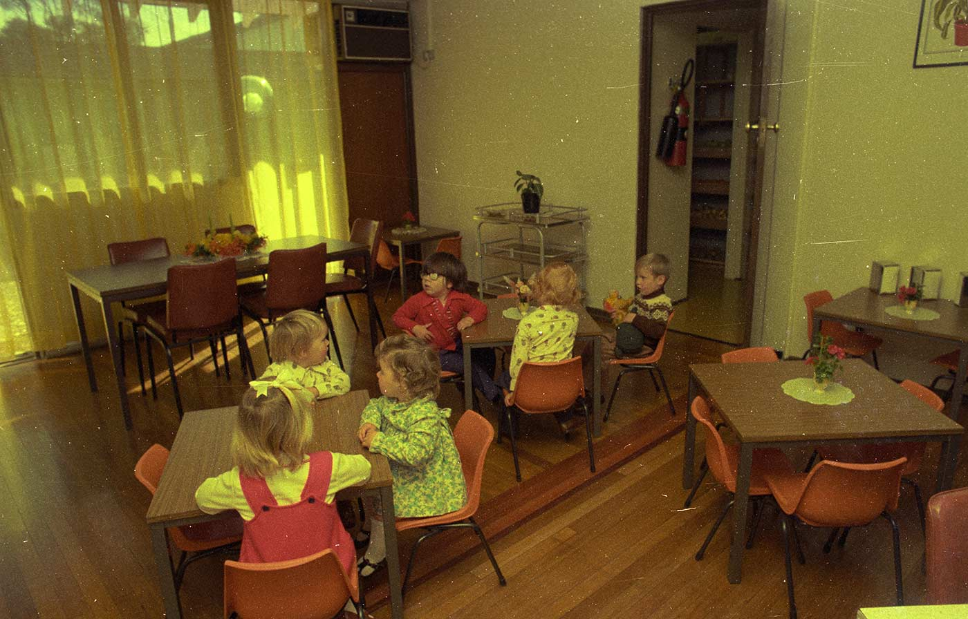 Colour photo showing a dining room with four small, brown veneer-topped tabled tables with chairs of orange moulded plastic. Two groups of three small children sit at the central tables. A larger table sits to the left. - click to view larger image