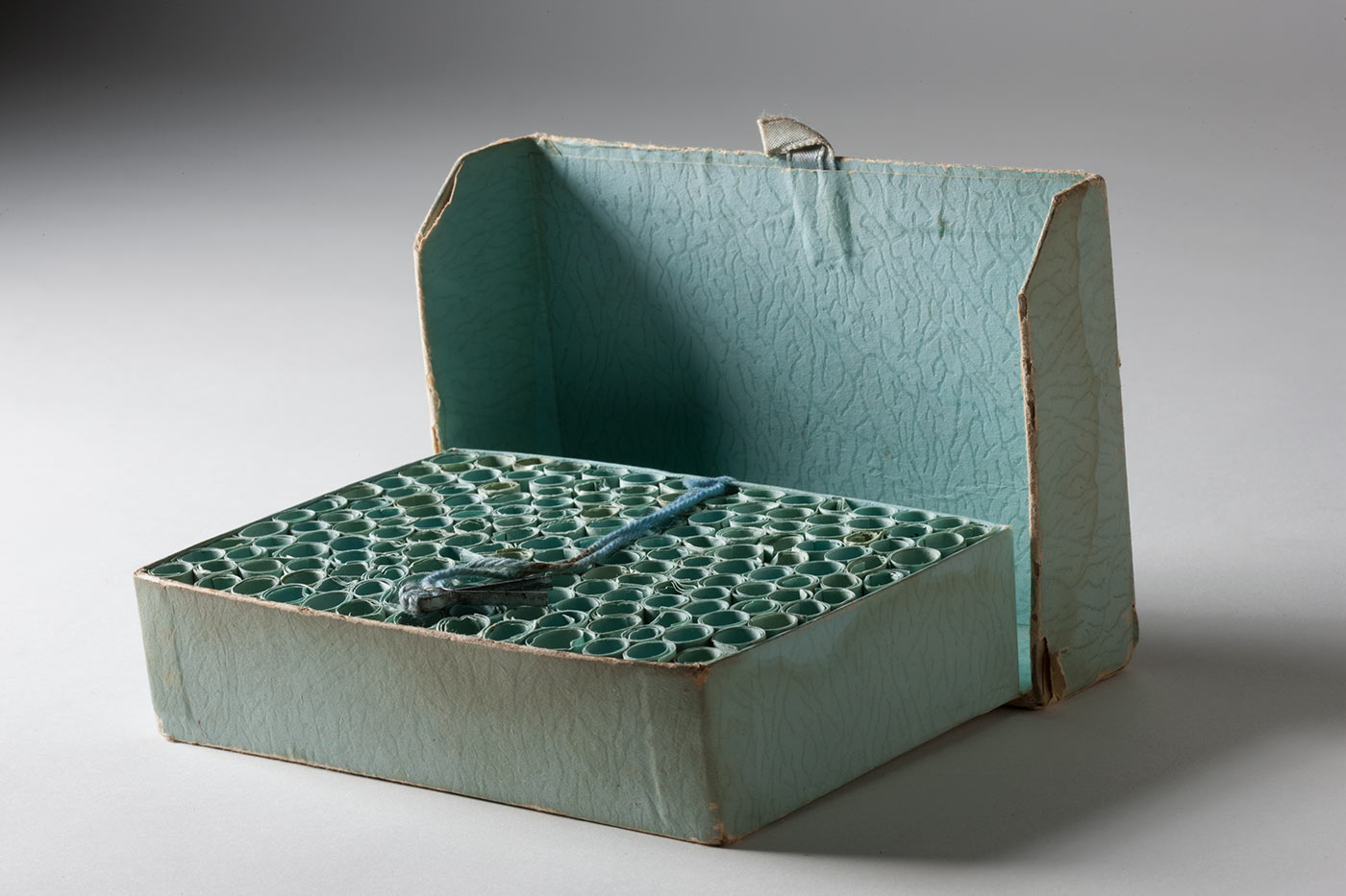 A pale blue-green box with its hinged lid open. Inside are small scrolls of rolled pape blue paper. A piece of wool and metal clasp rests on top. - click to view larger image