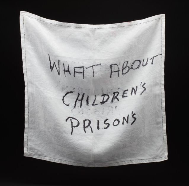 White square damask table napkin with 'WHAT ABOUT / CHILDREN'S / PRISONS' handwritten in black marker pen. - click to view larger image