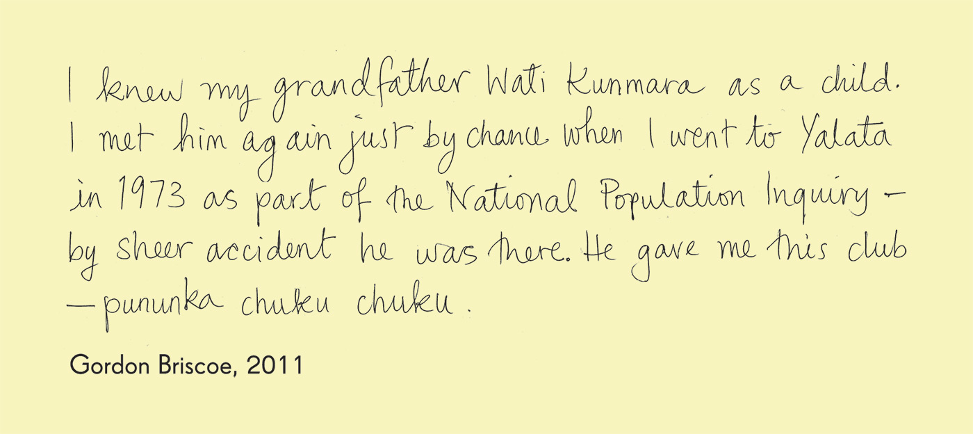 Exhibition graphic panel that reads: 'I knew my grandfather Wati Kunmara as a child. I met him again just by chance when I went to Yalata in 1973 as part of the National Population Inquiry — by sheer accident he was there. He gave me this club — pununka chuku chuku', attributed to 'Gordon Briscoe, 2011'. - click to view larger image