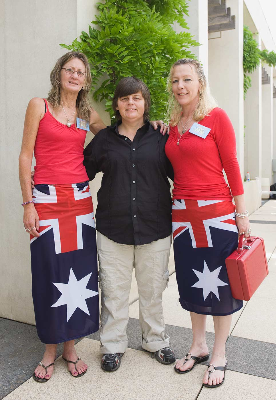 Colour photograph showing three women standing outside a buildling. The women on either side wear red tops and Australian flags as skirts. - click to view larger image