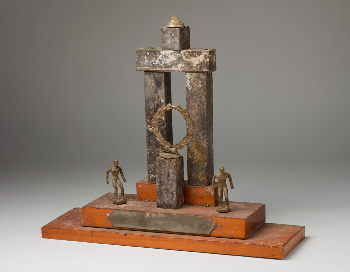 A trophy with a stepped wooden base, a metal 'triumphal arch' feature, a pillar with a laurel wreath and a male and female figure either side. The trophy is streaked with bird droppings. - click to view larger image
