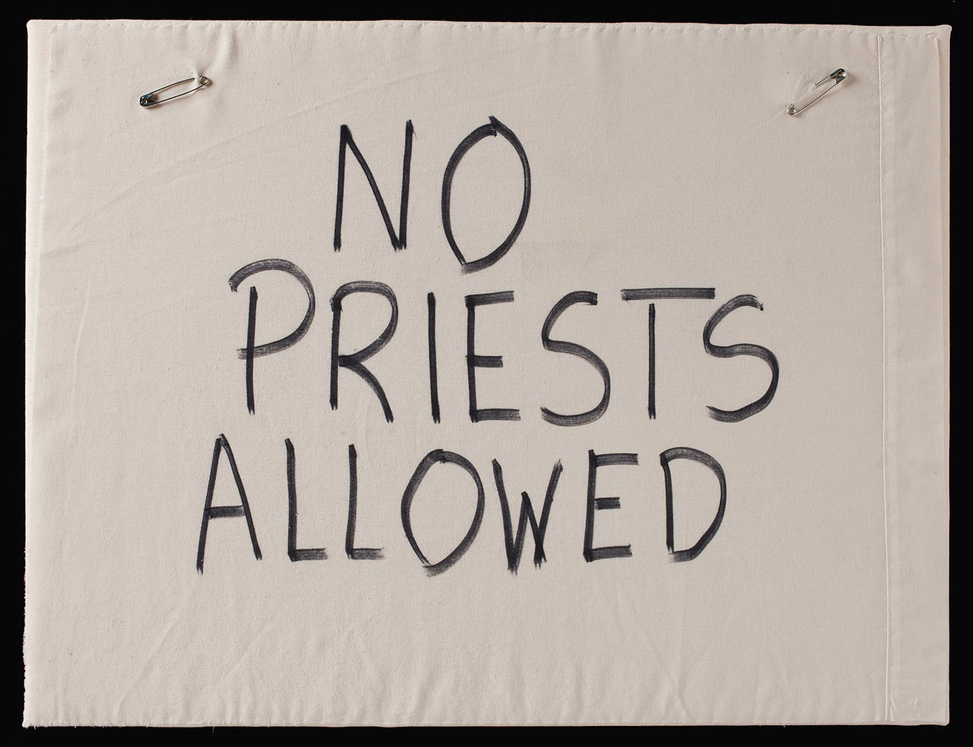 A photograph of a piece of off-white cloth with 'NO PRIESTS ALLOWED' handwritten in black capital letters. Safety pins are attached to the top corners. - click to view larger image