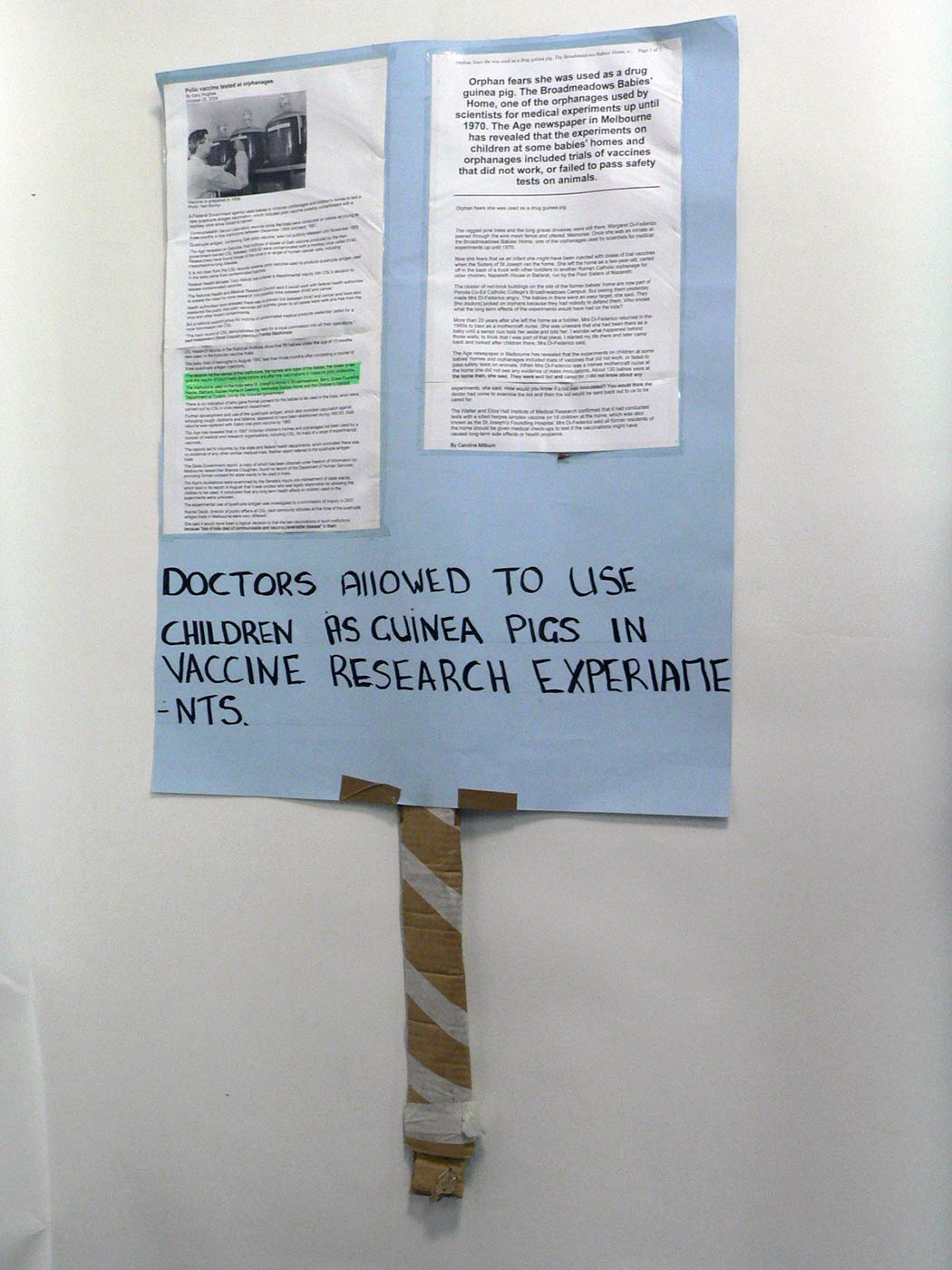 A placard made of a piece of pale blue cardboard with two computer printouts attached. Handwritten text across the bottom reads: 'DOCTORS ALLOWED TO USE CHILDREN AS GUINEA PIGS IN VACCINE RESEARCH EXPERIAMENTS.' The placard is attached to a piece of rolled brown cardboard with masking tape wrapped around it. - click to view larger image