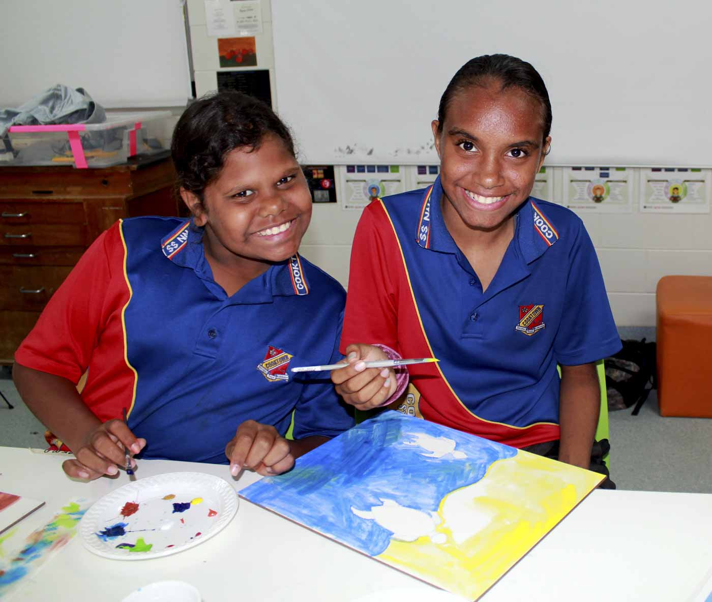Two girls in a red and blue uniform smile at the camera while working on paintings. - click to view larger image