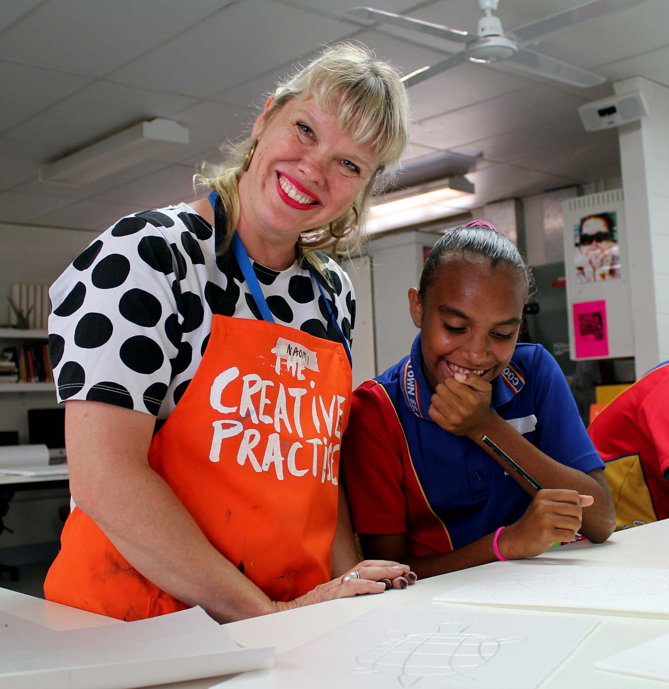 A woman wearing an apron that reads 'Creative Practice' smiles at the camera, while standing beside a female school student, seated at a desk.  - click to view larger image