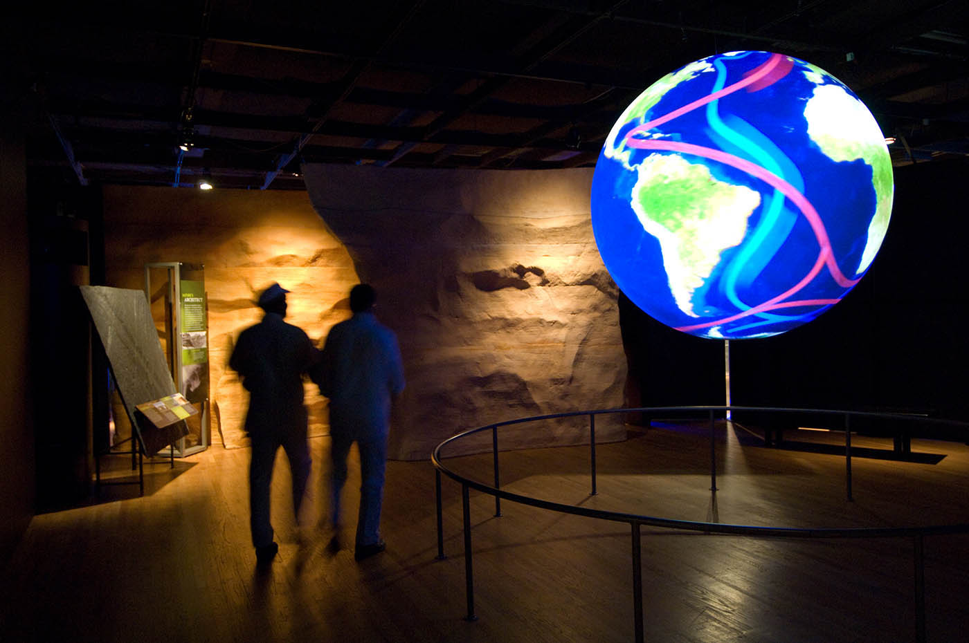Two silhouetted visitors look at a large globe showing South America surrounded by a sea marked with multi-coloured water currents.
