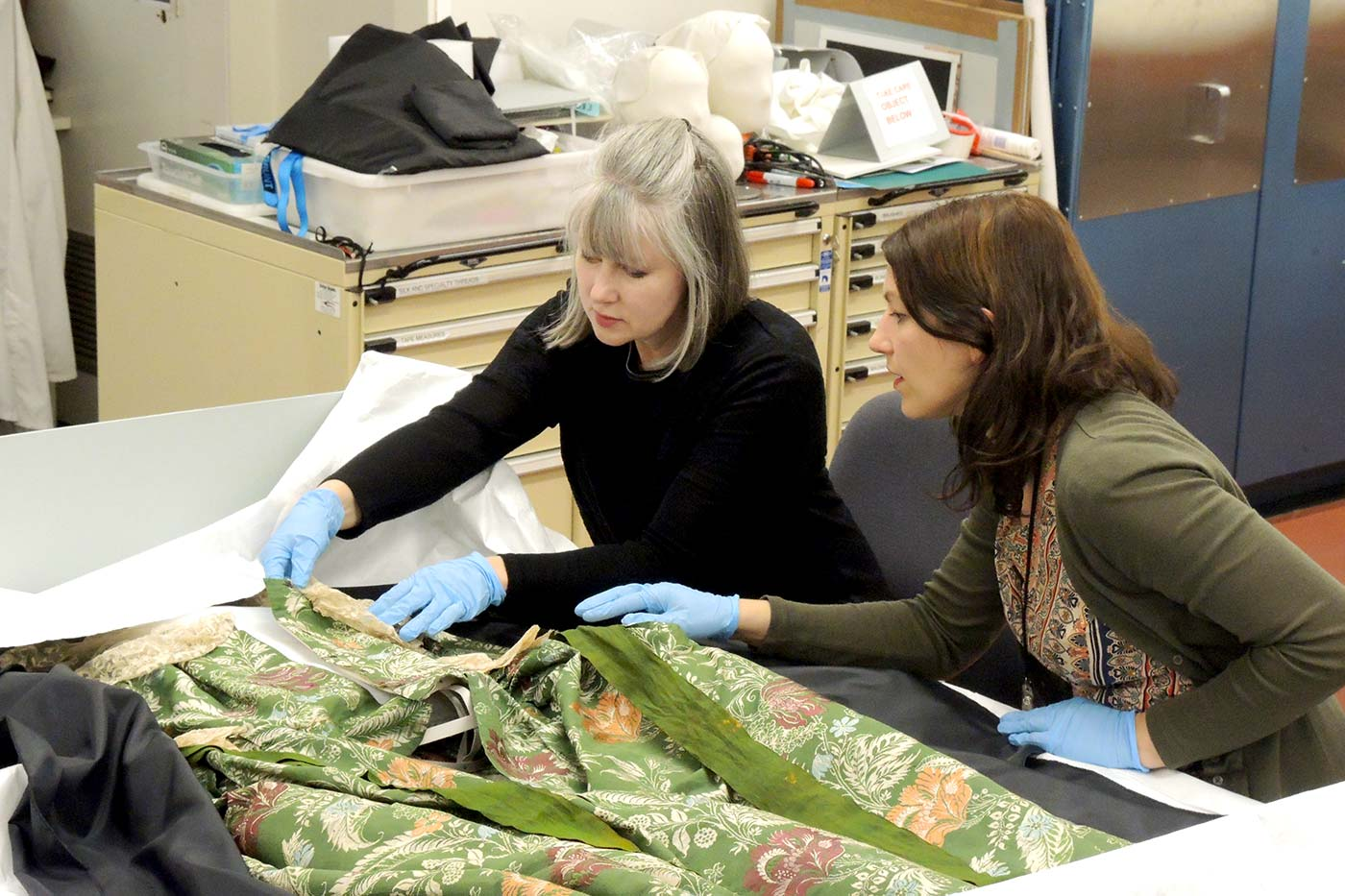 Two female conservators work on a dress with intricate pattern and lace detail in a laboratory.