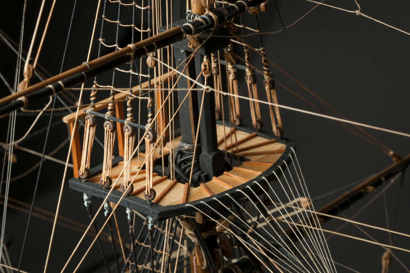 Detail image srom a small wooden sailing ship showing a platform on a mast, surrounded by rope rigging. - click to view larger image