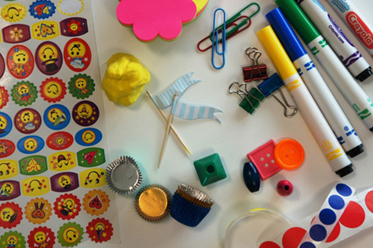 A variety of items that could be used to make a board game including paperclips, stickers, pens, buttons and modelling clay.
