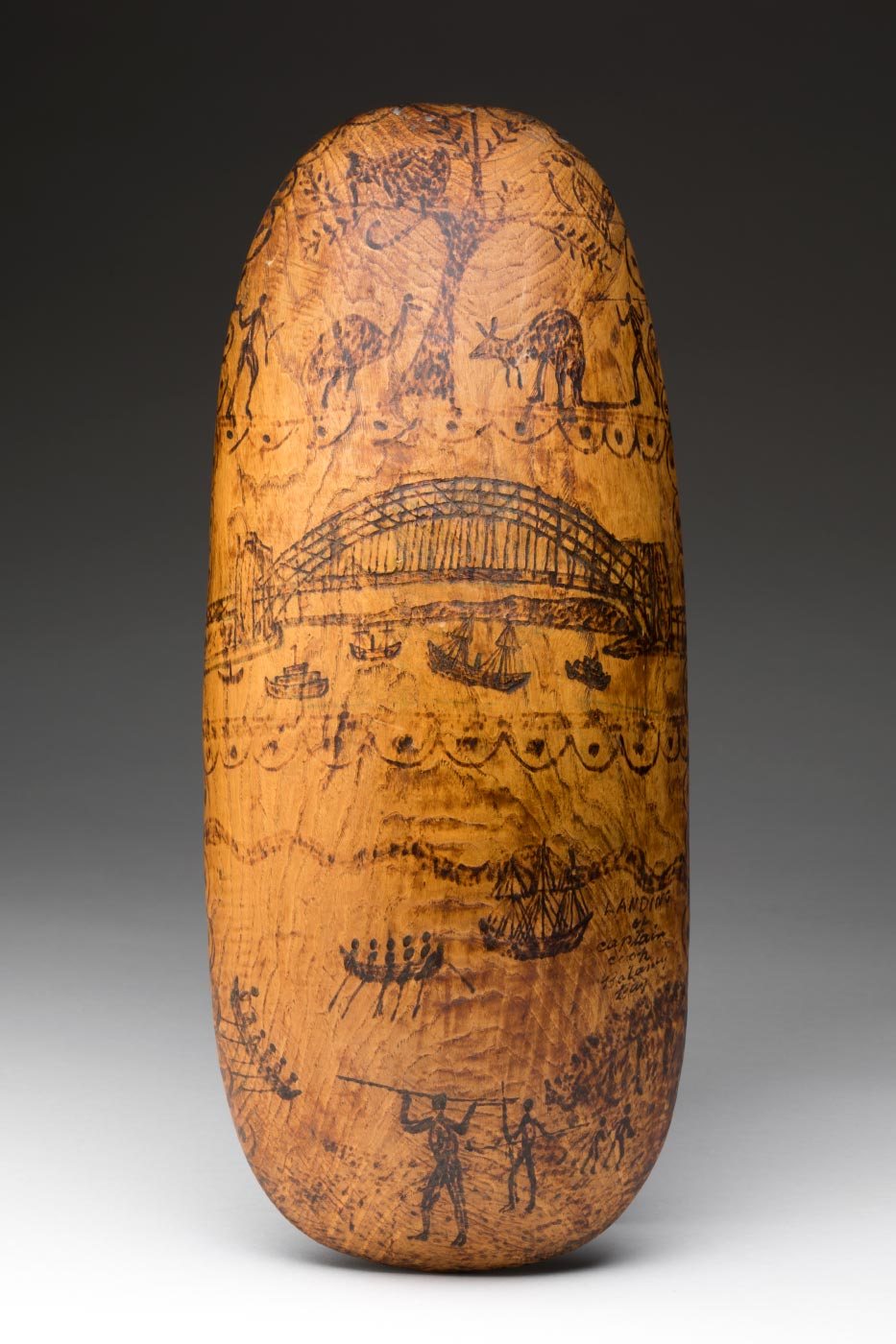 Wooden shield with illustrations of Australiana etched into surface.