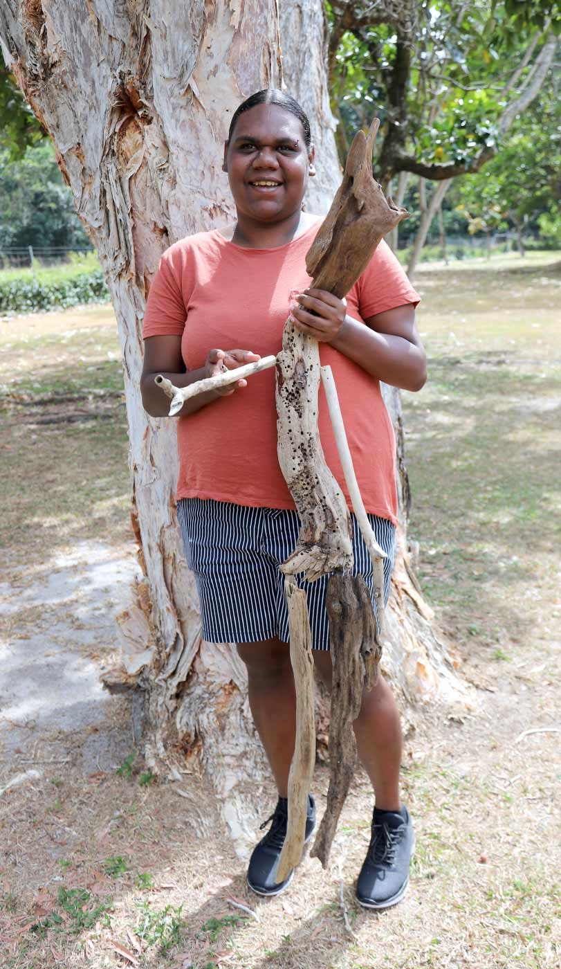 A female artist holds up her sculpture made from driftwood and other materials. - click to view larger image