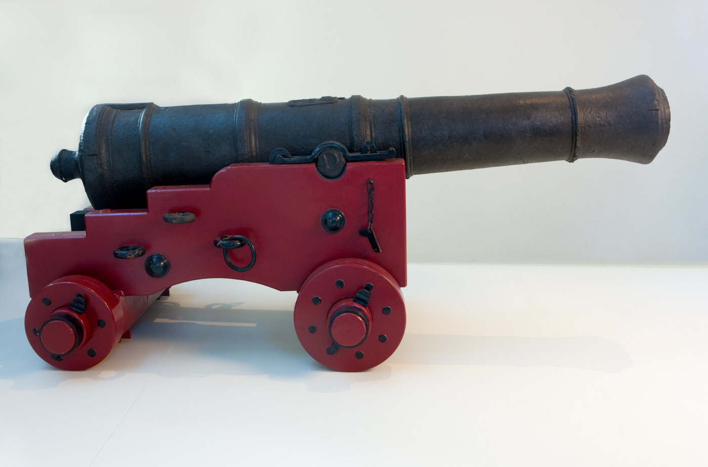 Colour photo of a cast-iron cannon mounted on a red base on wheels. - click to view larger image