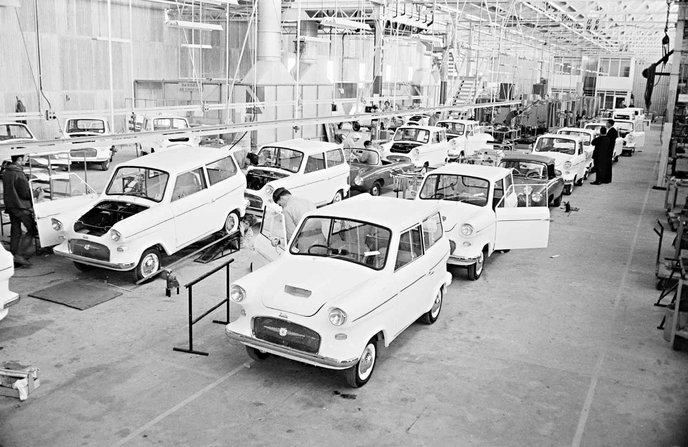 A black and white image of a row of cars on a mass production line.