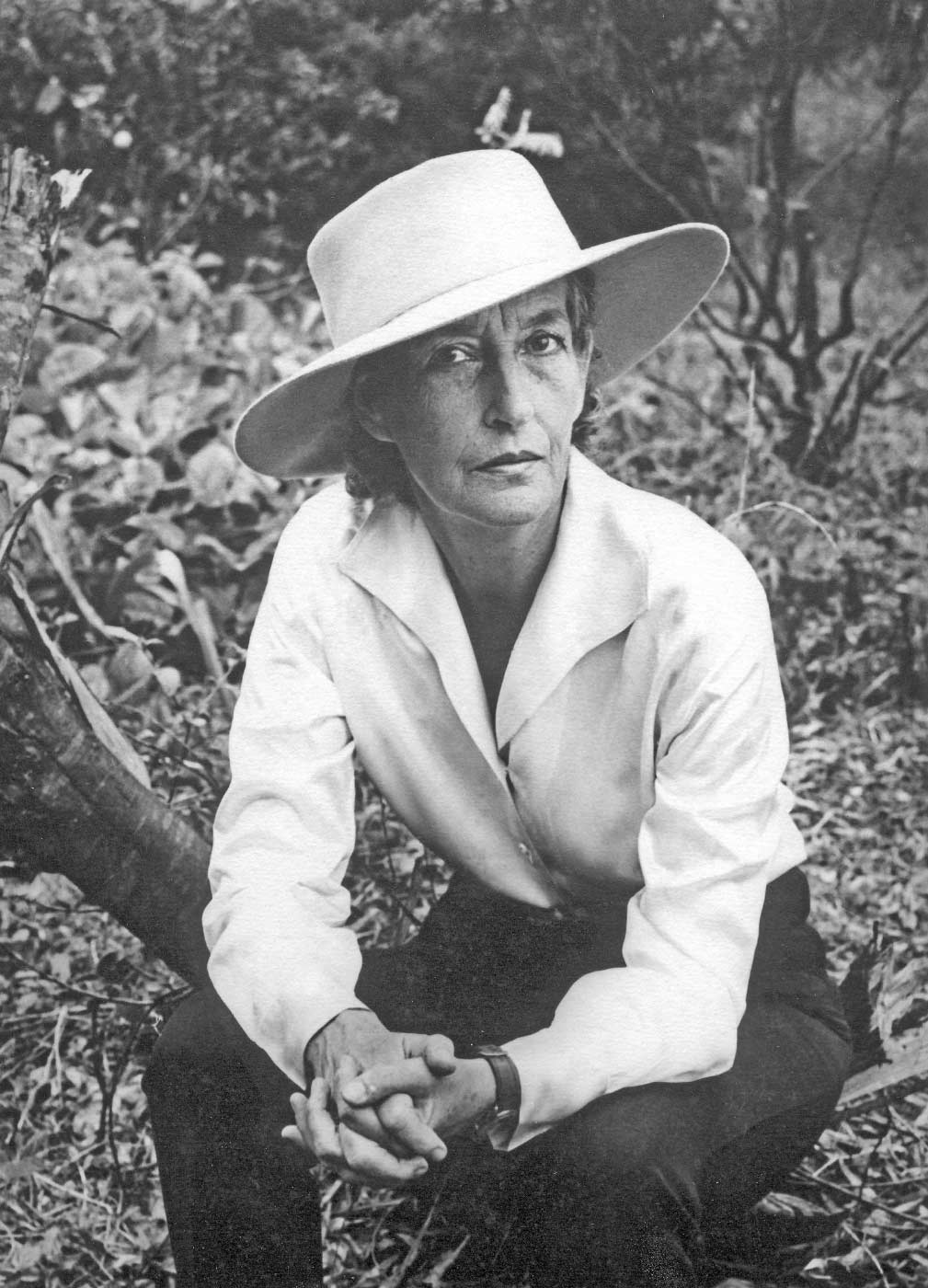 Black and white portrait of a woman sitting in bushland and wearing a wide-brimmed hat, shirt and trousers. - click to view larger image