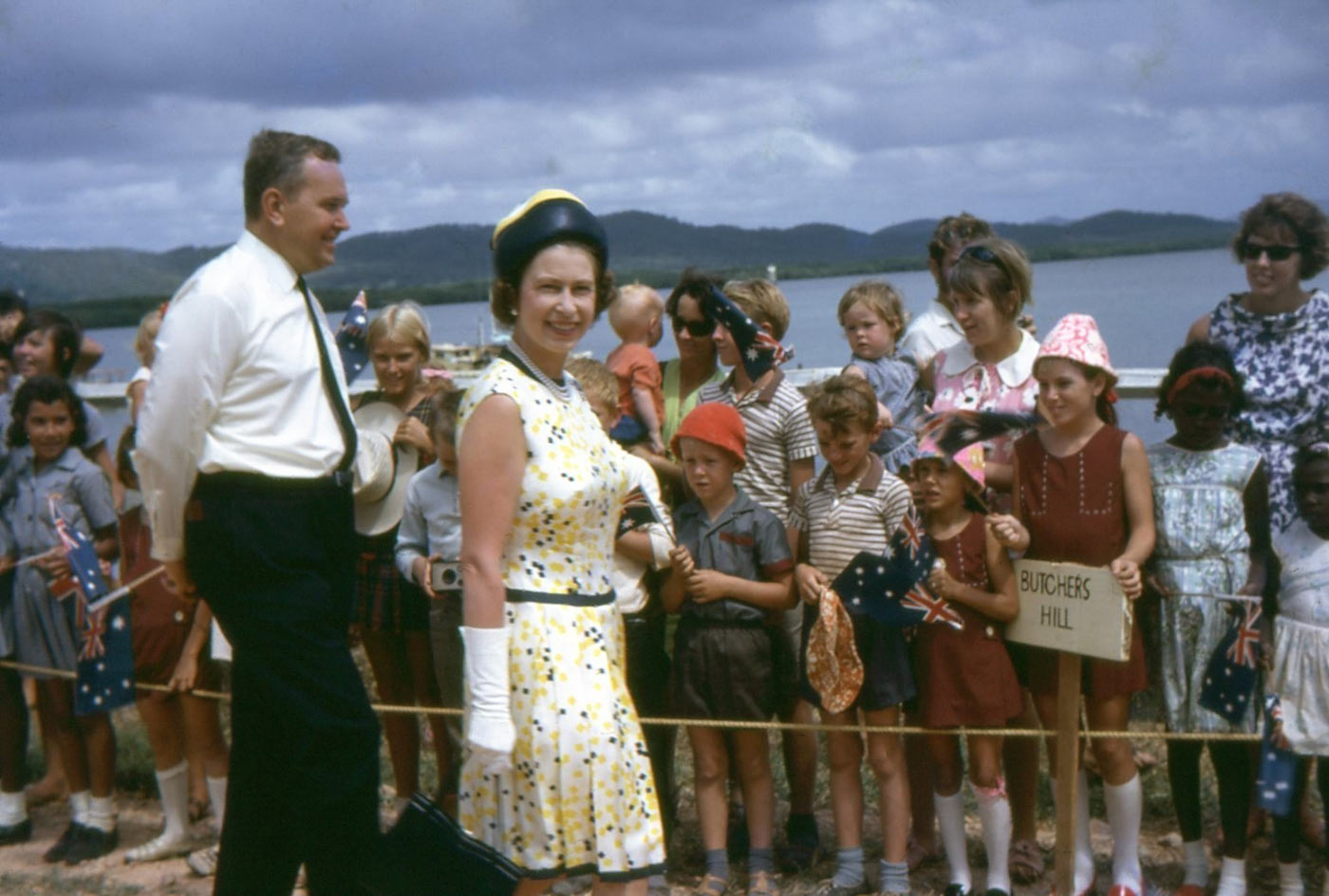 Colour photo of Queen Elizabeth II being greeted by town residents. There is a girl holding a sign that reads 'BUTCHERS HILL'. - click to view larger image