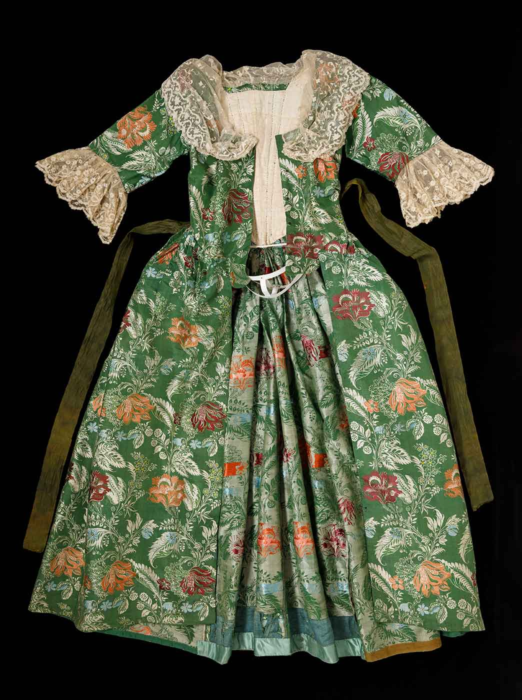 The front of a green and floral dress with lace trim on the sleeves and collar with a long green sash like belt stitched at the waist. - click to view larger image