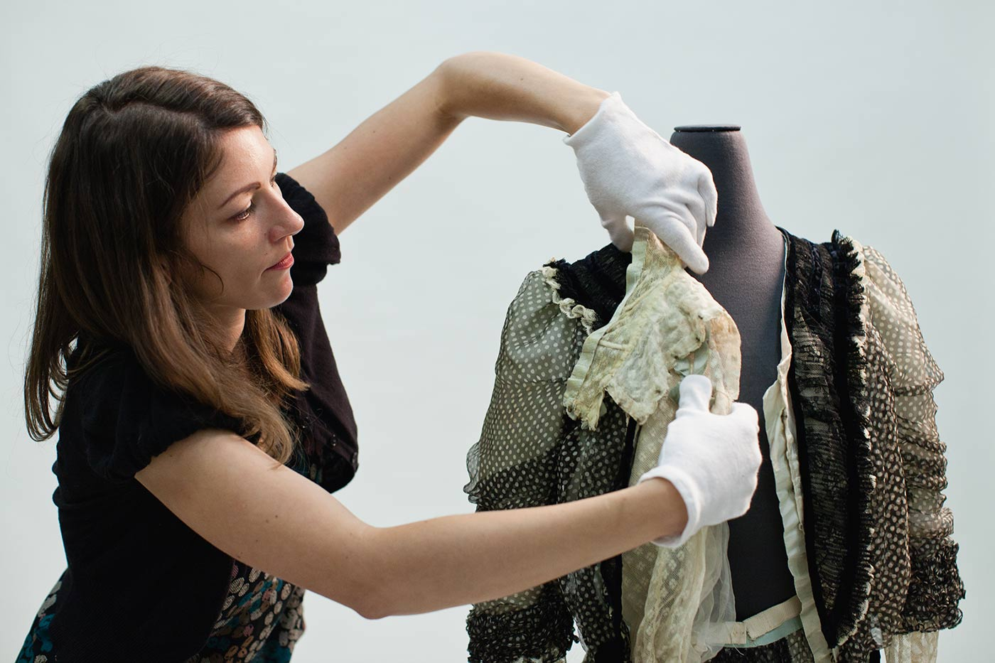 A conservator arranges the front of a bodice. - click to view larger image