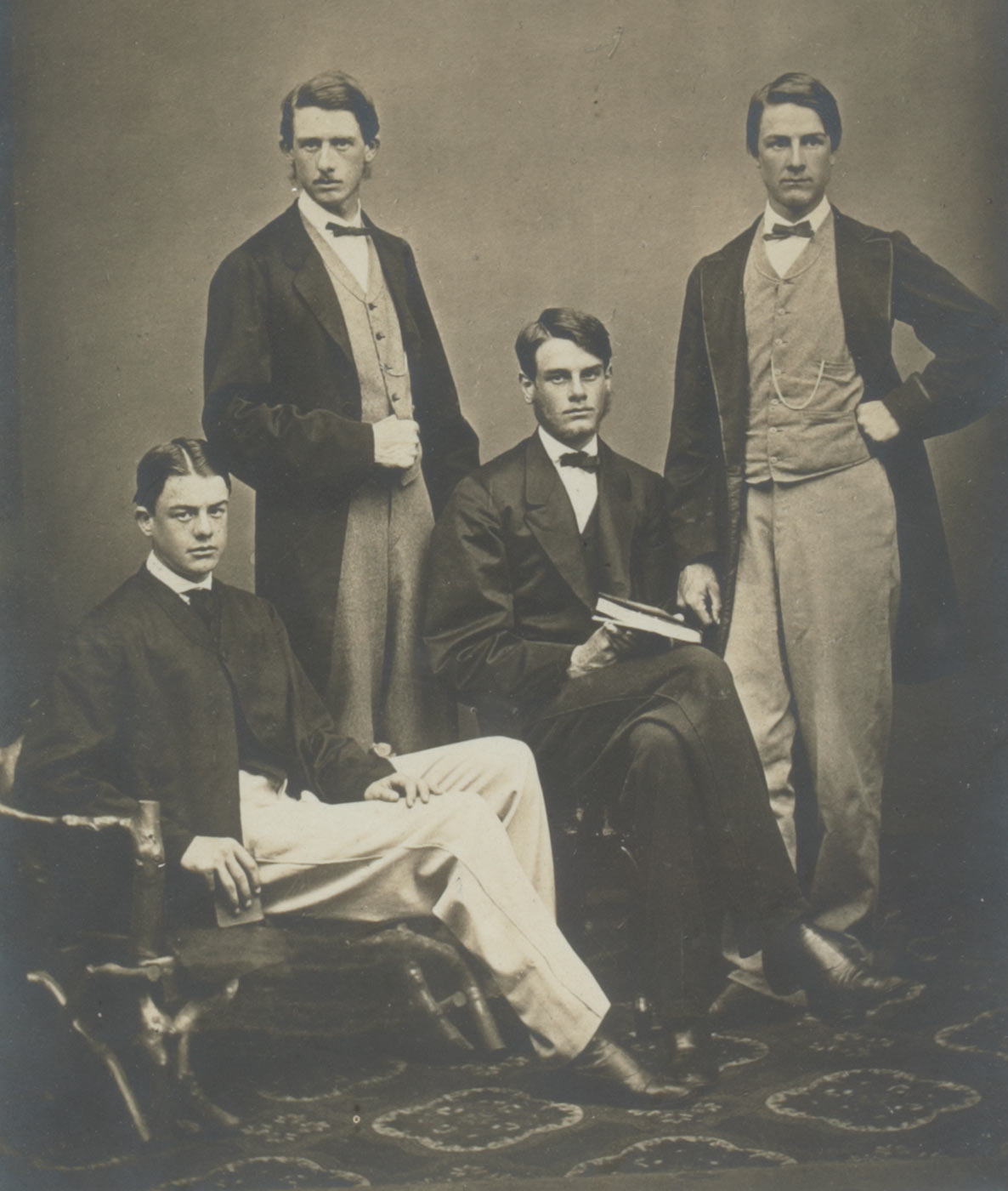 A black and white portrait photograph of four men, two seated and two standing, all wearing suits and bowties. The photograph is set on a grey mount and in a light brown wooden frame with recessed gold interior edging. It depicts standing, on left, William Percy, on right, George Ernest; seated on left, Reginald, on right Henry Montague. Handwritten on mount