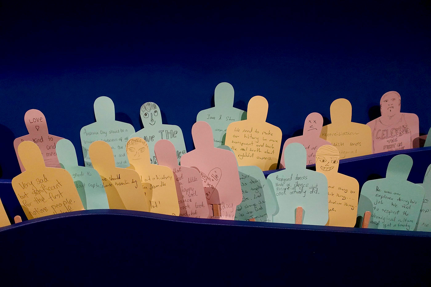 Exhibition display featuring multiple pieces of coloured paper cut out in the shape of people - some with faces - with hand written messages.