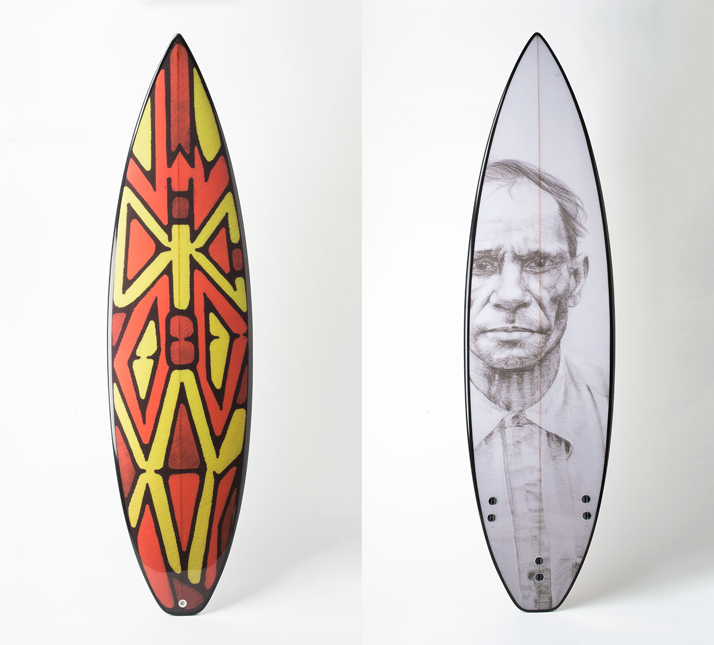 From left to right of the image, front and back of a surfboard and an etching resembling a shield. - click to view larger image